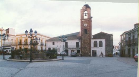Plaza de España con la Fuente en el centro y la Torre del Reloj al fondo.